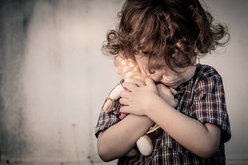 sad little boy hugging a doll