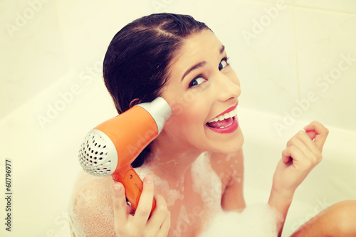 Woman in bath with electric dryer