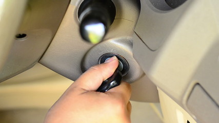 Male hand starting a car engine with ignition key