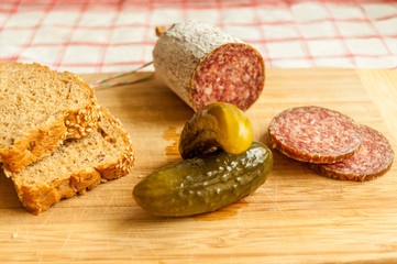 Salami slices with pickles on wood background