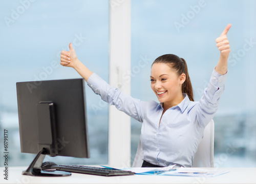 woman with computer, papers showing thumbs up