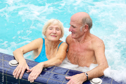 Happy healthy senior couple having fun together in jacuzzi