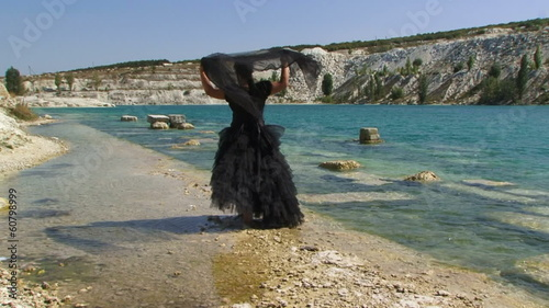 Lady in black on a shore of a lake