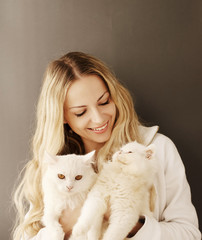 Girl holding two Persian cats