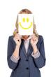 Frau hält sich lachenden Smiley vor das Gesicht
