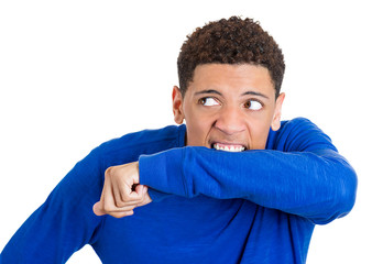 Crazy, insane young man biting his arm