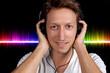 Junger lachender Mann hört Musik über Kopfhörer