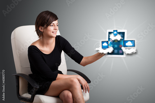 young woman holding tablet with modern devices in clouds