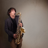 Young musician playing on saxophone
