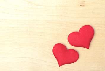 two red hearts on a wooden  board