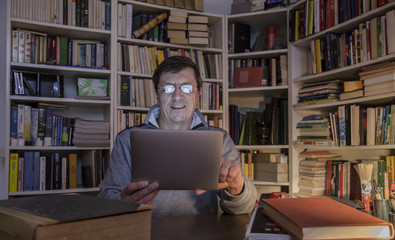 Mature man surrounded by books but read on your tablet