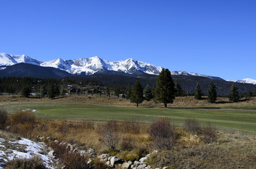 Golf course by the snow covered mountains