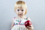 Serious little girl holds  a red apple