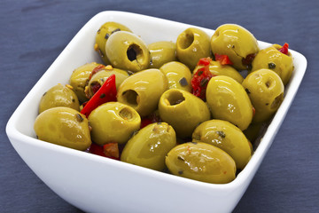Spicy green olives in a china dish.