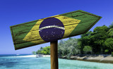 Brazil flag wooden sign with a beach on background