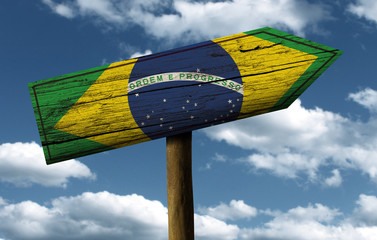 Brazil flag wooden sign with a beautiful sky on background