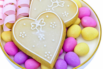 Two heart shaped cookies on a late with sugared almonds.