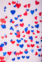 Background of red and blue paper hearts hanging on strings
