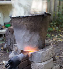flame from a gas burner heats the bucket