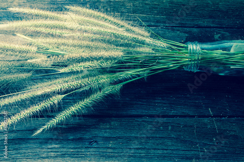 grass and glass bottle on old wooden