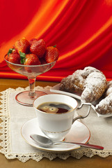 Breakfast with coffee , fresh croissants and strawberries.