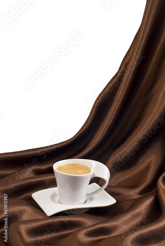 Composition with cup of coffee over brown satin.