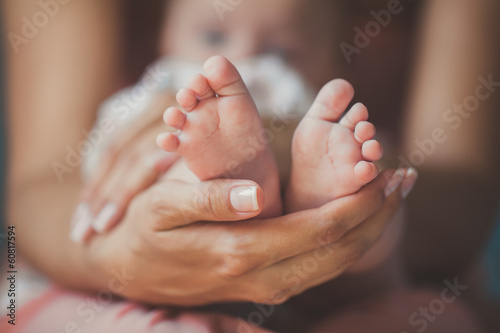 Masseur massaging little baby's foot, shallow focus