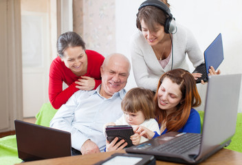family of three generations uses few various electronic device