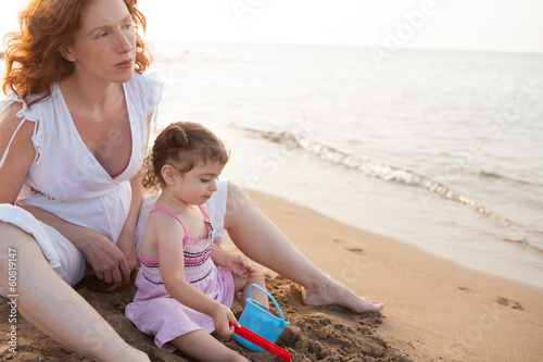pregnant mother and daughter playing in beach sand