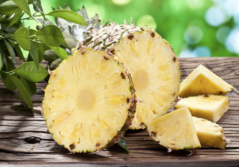 Pineapple with slices on a wooden table.