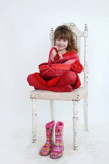 Girl in red holding red wicker basket, boots down on the floor