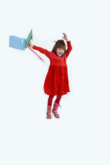 Happy girl in red flying and jumping with colorful shopping bags