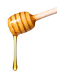 Honey dripping from wooden honey dipper isolated on white