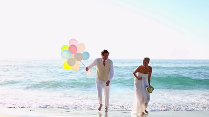 Newlyweds laughing and playing with balloons on the beach