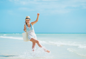 Young woman with hat and bag having fun time at seaside