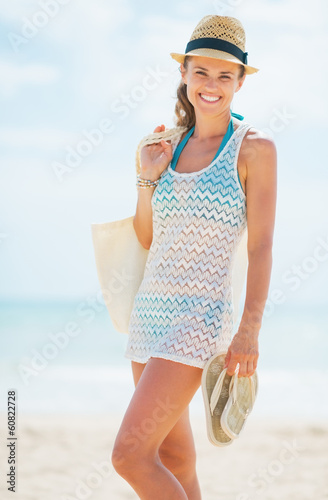 Happy young woman in hat and with bag on beach