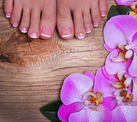 Pedicure with pink orchid flowers on wooden background.