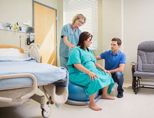 Nurse And Man Assisting Pregnant Woman On Exercise Ball