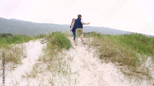 Siblings playing on the sand dunes