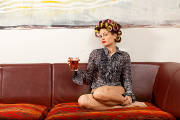 sexy girl drinking a drink on the couch