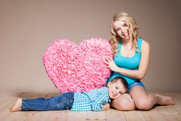 young woman with her son while holding a heart shape sign