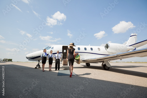 canvas print picture Rich Woman Walking Towards Private Jet At Airport Terminal