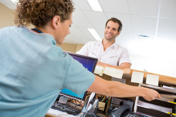 Man Looking At Nurse Working At Reception Desk