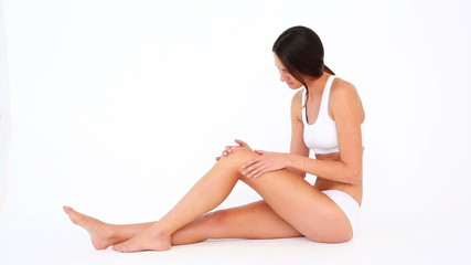 Fit woman touching her sore knee and shaking her head