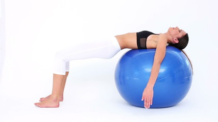 Fit model doing pelvic lifts on blue exercise ball