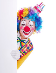 Happy girl clown in birthday cake hat holding the blank board