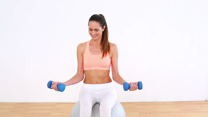 Fit model sitting on exercise ball lifting dumbbells