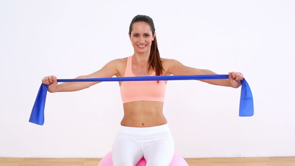 Fit model sitting on exercise ball stretching resistance band