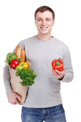 young man holding shopping bag full of groceries on white