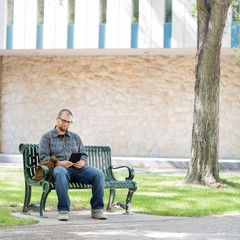 University Student Using Digital Tablet On Bench
